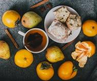 Чай, ручки циннамона, булочки, груши, анисовка звезды и хурмы Стоковая Фотография