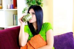 Чай счастливой женщины ослабляя выпивая травяной дома Стоковые Фотографии RF