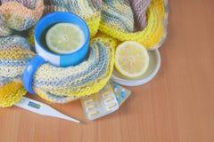 Чай с лимоном, термометром, пилюльками и связанным одеялом Стоковые Изображения