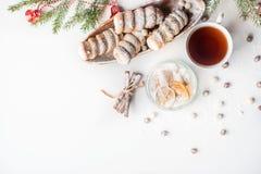 Чай с печеньями, ветвь рождества спруса зеленого цвета, разбросанных печениь, печенья улитки с сливк протеина Стоковая Фотография RF