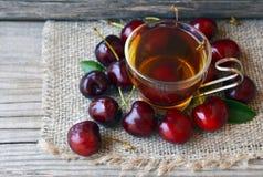 Чай с свеже выбранными вишнями в стеклянной прозрачной чашке на ткани мешковины Чай льда вишни плодоовощ на старом деревянном сто Стоковая Фотография RF