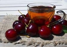Чай с свеже выбранными вишнями в стеклянной прозрачной чашке на ткани мешковины Чай льда вишни плодоовощ на старом деревянном сто Стоковое Фото