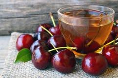 Чай с свеже выбранными вишнями в стеклянной прозрачной чашке на ткани мешковины Чай льда вишни плодоовощ на старом деревянном сто Стоковая Фотография