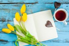 Чай, тюльпаны и тетрадь на голубой таблице Стоковые Изображения