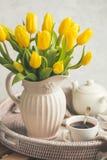 Чай утра на подносе и желтых тюльпанах Стоковое Фото