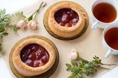 Чай утра с хлебобулочными изделиями, розовыми цветками на таблице Торт с клубниками На старой салфетке Стоковое Изображение RF