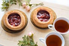 Чай утра с хлебобулочными изделиями, розовыми цветками на таблице Торт с клубниками На старой салфетке Стоковые Фотографии RF