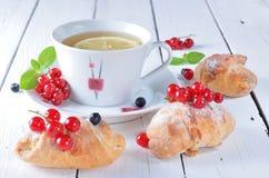 Чай утра, ягоды красной смородины и круассаны на деревянном tabl Стоковая Фотография RF