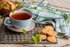 чай чашки зеленый Чашка чаю с круглым печеньем на зеленой linen checkered салфетке и винтажным железным подносом, листьями зелено Стоковое Изображение