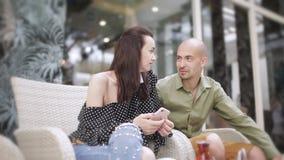 Чай человека и женщины выпивая в кафе улицы и наблюдая фото на smartphone сток-видео
