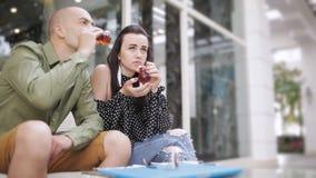 Чай человека и женщины выпивая в кафе улицы и наблюдая фото на smartphone акции видеоматериалы