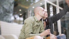 Чай человека и женщины выпивая в кафе улицы и selfies принимать на smartphone сток-видео