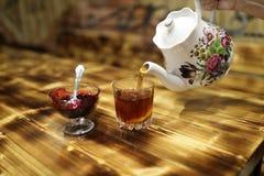 Чай человека лить от керамического чайника стоковая фотография