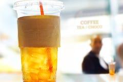 Чай льда лимона в пластичных стеклах на предпосылке ресторана Стоковая Фотография