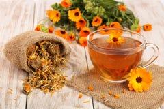 Чай Calendula с свежими и высушенными цветками на белой деревянной предпосылке Стоковая Фотография