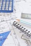 Чалькулятор, блокнот и чертегные инструменты аранжированные на планах Стоковое Фото