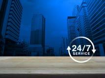 24 часа обслуживают значок на деревянном столе над современным городом офиса к Стоковые Изображения RF