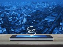 24 часа обслуживают значок на современном умном экране телефона на таблице Стоковые Изображения