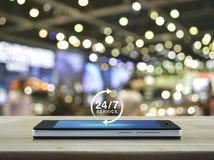 24 часа обслуживают значок на современном умном экране телефона на таблице Стоковое Фото
