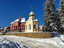 Часовня с стороной Святого на стене и купола взбрызнутой с снегом Стоять около дома большого кирпича частного Стоковое Изображение
