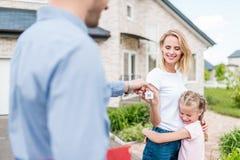 частично взгляд агента недвижимости давая ключ молодой женщине стоковое фото