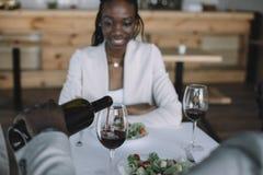 частично взгляд Афро-американского лить вина в стекло во время романтичной даты с девушкой стоковое фото