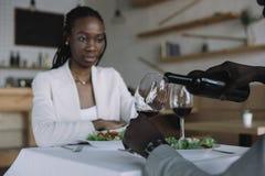 частично взгляд Афро-американского лить вина в стекло во время романтичной даты с девушкой стоковые фото