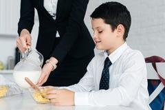 частично взгляд женщины в молоке костюма лить в шар сыновей с завтраком стоковые фото