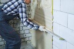 Частично взгляд построителя штукатуря на стене блока стоковые фото