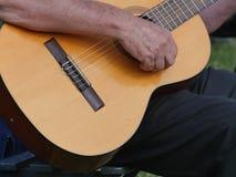 Частично взгляд прямо сыгранной деревянной trekking гитары, строки отбрасывая, рука клал дальше для того чтобы сыграть стоковые изображения