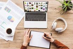 частично взгляд человека делая примечания в тетради на рабочем месте с компьтер-книжкой с pinterest вебсайтом, бумаги, чашку кофе стоковая фотография