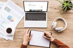 частично взгляд человека делая примечания в тетради на рабочем месте с компьтер-книжкой с вебсайтом airbnb, бумаги, чашку кофе стоковые фото