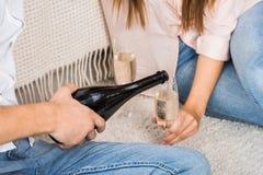частично взгляд шампанского человека лить в стекло пока сидящ на поле вместе с девушкой стоковая фотография rf