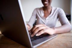 Частично портрет усмехаясь женщины сидя на столе и печатая на портативном компьютере Стоковое фото RF