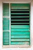 Частично раскройте откалыванные зеленые штарки в окне на белой стене Стоковое фото RF