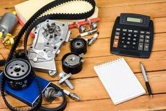 Части автомобиля и калькулятор на деревянном столе стоковая фотография rf