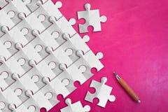 Части головоломки белой бумаги на розовой кожаной предпосылке jpg Стоковые Изображения