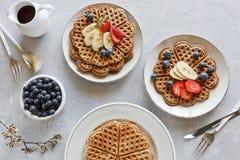 Части домодельного waffle испекут с бананом и голубиками на плитах на серой предпосылке Стоковая Фотография RF