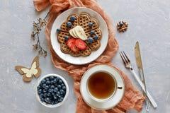 Части домодельного waffle испекут с бананом и голубиками на плитах на серой предпосылке Стоковое Изображение RF