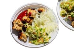 Части зажаренного мяса с луком и салатом на плите стоковые фото