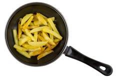Части зажаренных картошек в сковороде изолированной на белизне Стоковые Изображения RF