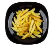 Части зажаренных картошек в черной плите изолированной на белизне Стоковая Фотография