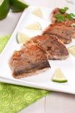 Части зажаренных рыб на квадратной плите Стоковое Изображение