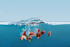 Части зрелых клубник падая в воду с брызгают Стоковое Фото