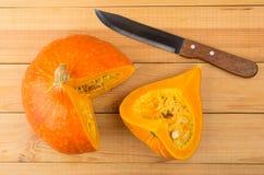 Части зрелых тыквы и кухонного ножа на деревянном столе Стоковые Изображения RF