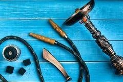 Части кальяна на голубой деревянной предпосылке Accessorie кальяна Стоковое Изображение RF