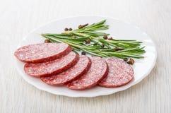 Части копченых сосиски, розмаринового масла, перца и гвоздики внутри plat Стоковое Фото