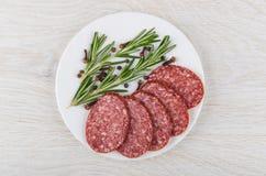 Части копченых сосиски, розмаринового масла, перца и гвоздики внутри plat Стоковая Фотография RF