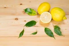 Части лимона в листьях на светлой деревянной предпосылке Стоковые Фото