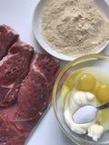 Части лож мяса на разделочной доске Рядом с контейнером ингридиенты для бэттера: майонез, яичко и соль Стоковые Фотографии RF